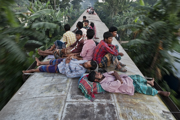 Bangladeshis sleep on the roof of a moving train as they rush home to their respective villages to be with their families in Dhaka, Bangladesh.